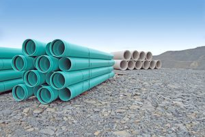Stacked PVC water pipe and concrete storm sewer pipe on a new road construction site.